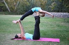 2 vrouwen doen de yogavorm acro yoga